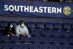 Fans wear masks and sit in marked-off seats at an NCAA college basketball game in the Southeastern Conference tournament Wednesday, March 10, 2021, in Nashville, Tenn. Large buildings with high ceilings and ventilation systems that can change out fresh air almost a third as well as airplanes are reasons why experts and engineers believe it's reasonable for limited numbers of fans to be returning to live, indoor sporting events. They say masks are still necessary, but most professional and big college arenas – like the ones that host NHL and NBA games and the NCAA Tournament – have the capacity to make it work and keep people from spreading the coronavirus. (AP Photo/Mark Humphrey)