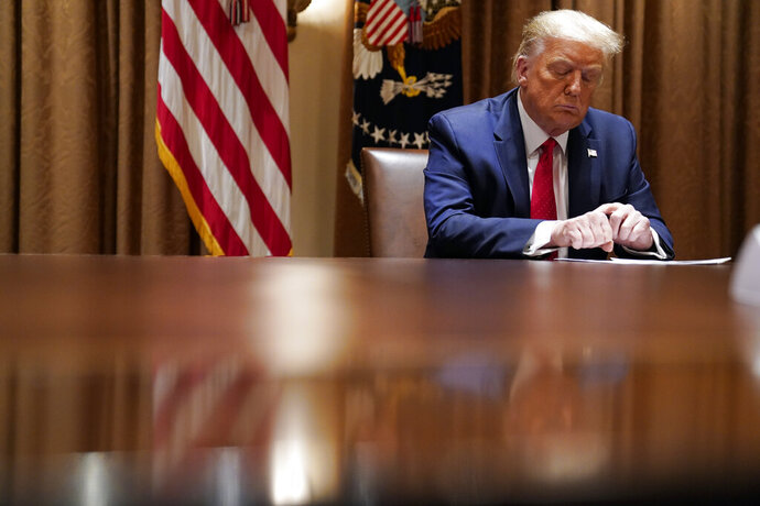 """FILE - In this July 9, 2020, file photo President Donald Trump listens during a meeting with Hispanic leaders in the Cabinet Room, Thursday, July 9, 2020, in Washington. Republicans are trying to convince voters that the rare looting and violence that marred largely peaceful social justice protests foretell a wave of mayhem to come if Democrats are elected in November. Trump emphasized that menacing theme at the White House on Thursday, calling proponents of defunding the police """"crazy."""" Noting to a visiting group of Hispanic Americans that many immigrants had fled dangerous countries, Trump added, """"They know what happens when the police cannot protect the innocent, when the rule of law is destroyed."""" (AP Photo/Evan Vucci, File)"""