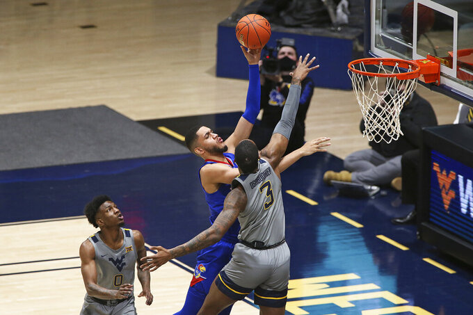 Kansas guard Tristan Enaruna (13) shoots while defended by West Virginia guard Kedrian Johnson (0) and forward Gabe Osabuohien (3) during the first half of an NCAA college basketball game Saturday, Feb. 6, 2021, in Morgantown, W.Va. (AP Photo/Kathleen Batten)