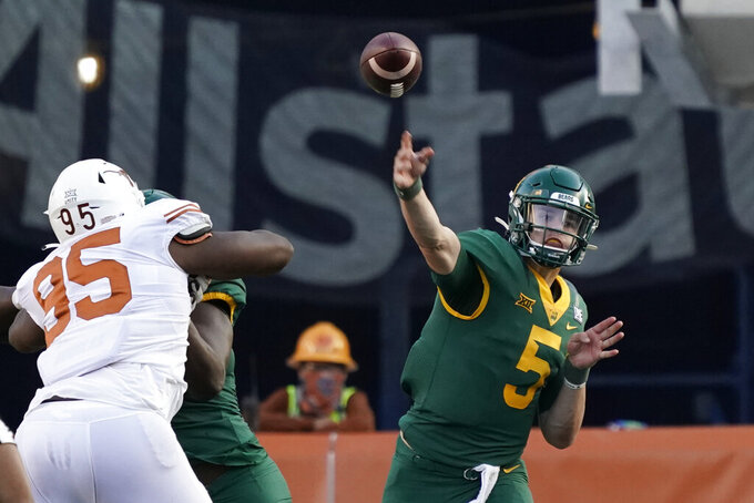 Baylor's Charlie Brewer (5) passes as Texas' Alfred Collins (95) defends during the second half of an NCAA college football game in Austin, Texas, Saturday, Oct. 24, 2020. (AP Photo/Chuck Burton)