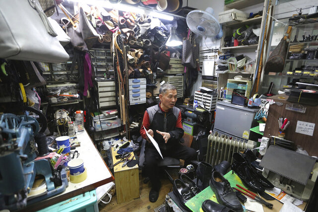 In this March 25, 2020 photo, South Korean shoe repairman Kim Byung-rok speaks during an interview at his shop in Seoul, South Korea.  Kim is in news after he revealed plans to donate his property to help support people facing economic difficulties amid the coronavirus outbreak. Kim says he wants to donate parts of his land on a small mountain near the border with North Korea that he bought in 2014. (AP Photo/Ahn Young-joon)