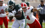 Michigan State running back Elijah Collins, left, runs for a touchdown against Youngstown State's Vinny Gentile during the first quarter of an NCAA college football game, Saturday, Sept. 11, 2021, in East Lansing, Mich. (AP Photo/Al Goldis)