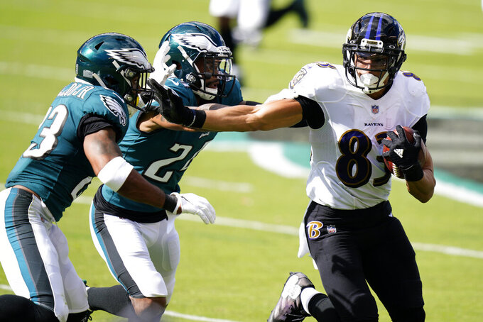 Baltimore Ravens' Willie Snead IV (83) tries to run past Philadelphia Eagles' Rodney McLeod (23) and Darius Slay (24) during the first half of an NFL football game, Sunday, Oct. 18, 2020, in Philadelphia. (AP Photo/Chris Szagola)