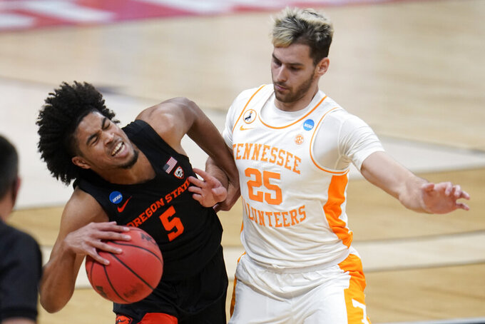 Tennessee guard Santiago Vescovi (25) fouls Oregon State guard Ethan Thompson (5) during the second half of a men's college basketball game in the first round of the NCAA tournament at Bankers Life Fieldhouse in Indianapolis, Friday, March 19, 2021. (AP Photo/Paul Sancya)