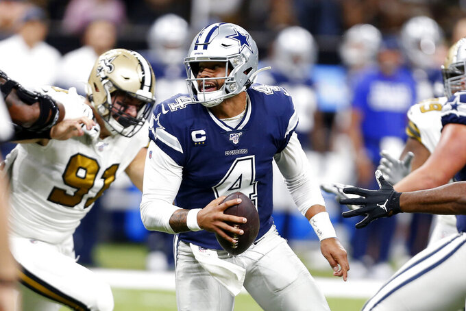 Dallas Cowboys quarterback Dak Prescott (4) scrambles under pressure from New Orleans Saints defensive end Trey Hendrickson (91) in the first half of an NFL football game against the New Orleans Saints in New Orleans, Sunday, Sept. 29, 2019. (AP Photo/Gerald Herbert)