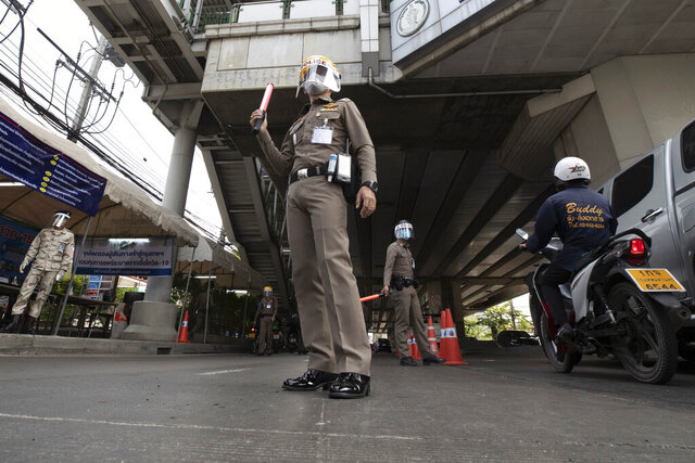 Policemen wearing face masks to protect themselves from the new coronavirus at a health checkpoint in Bangkok, Thailand, Friday, April 3, 2020. Thailand's prime minister announced a nationwide 10 p.m.-to-4 a.m curfew starting Friday to combat the spread of the coronavirus. The new coronavirus causes mild or moderate symptoms for most people, but for some, especially older adults and people with existing health problems, it can cause more severe illness or death. (AP Photo/Sakchai Lalit)
