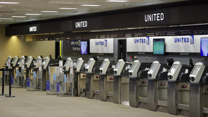 FILE - In this April 24, 2020 file photo, empty United Airlines ticket machines are shown at the Tampa International Airport in Tampa, Fla. United United Airlines will send layoff warnings to 36,000 employees - nearly half its U.S. staff - in the clearest signal yet of how deeply the virus outbreak is hurting the airline industry. United officials said Wednesday, July 8 that they still hope to limit the number of layoffs by offering early retirement, but they have to send notices this month to comply with a law requiring that workers get 60 days' notice ahead of mass job cuts. (AP Photo/Chris O'Meara, File)