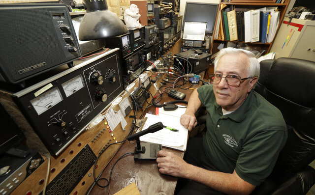 In this Friday, March 13, 2020 photo, Paul Buescher poses by his ham radio, in Northfield Center Township, Ohio. Buescher is one of 32 members of a group in northeastern Ohio that shares a farm packed with enough canned and dehydrated food and water to last for years. For those in the often-mocked