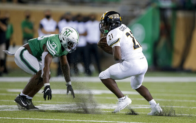 Southern Mississippi running back Frank Gore Jr. (21) looks for room against North Texas linebacker KD Davis (23) during the second half of an NCAA college football game on Saturday, Oct. 3, 2020, in Denton, Texas. (AP Photo/Brandon Wade)