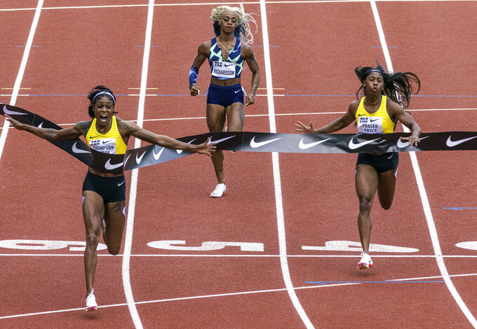 Jamaica's Elaine Thompson-Herah, left, wins the 100 meters, as American track and field sprinter Sha'carri Richardson, center, also competes, Saturday, Aug. 21, 2021, at the Prefontaine Classic track and field meet in Eugene, Ore. Richardson finished in last place. (AP Photo/Thomas Boyd)