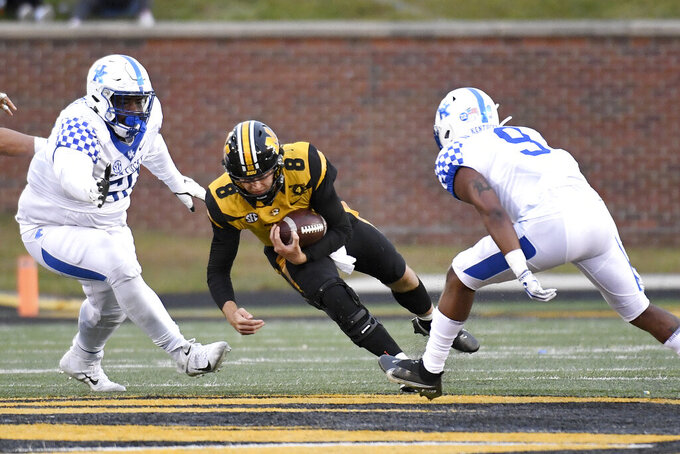 Missouri quarterback Connor Bazelak (8) dives for yardage as Kentucky defensive tackle Marquan McCall, left, and defensive back Davonte Robinson (9) defend during the second half of an NCAA college football game Saturday, Oct. 24, 2020, in Columbia, Mo. (AP Photo/L.G. Patterson)