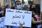 An anti-government protester holds an Arabic placard that reads: