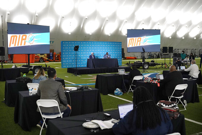 Miami Dolphins general manager Chris Grier, left, and coach Brian Flores, right, speak during a news conference about players chosen by the Dolphins in the first round of the NFL football draft, early Friday, April 30, 2021, in Davie, Fla. (AP Photo/Lynne Sladky)