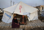 Syrians who are newly displaced by the Turkish military operation in northeastern Syria, sit in front of a tent upon their arrival at the Bardarash camp, north of Mosul, Iraq, Wednesday, Oct. 16, 2019. The camp used to host Iraqis displaced from Mosul during the fight against the Islamic State group and was closed two years ago. The U.N. says more around 160,000 Syrians have been displaced since the Turkish operation started last week, most of them internally in Syria. (AP Photo/Hussein Malla)