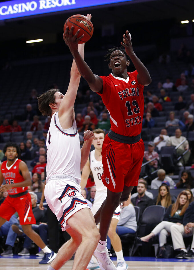Fresno State guard Aguir Agau, right, goes to the basket against Saint Mary's forward Kyle Bowen during the second half of an NCAA college basketball game in Sacramento, Calif., Wednesday, Nov. 20, 2019. Saint Mary's won 68-58. (AP Photo/Rich Pedroncelli)