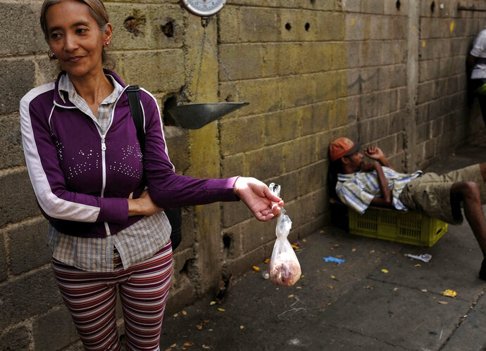 """In this May 11, 2018 photo, Vaceliza Villa holds a bag of raw chicken skin in an outdoor market, as a boisterous electoral campaign marches past, in Caracas, Venezuela. """"I really don't care what happens on Sunday,"""" said Villa, 47, holding up her bag of raw chicken skins to feed herself and her 6-year-old daughter for the week. """"My priority is paying for this.""""  (AP Photo/Fernando Llano)"""
