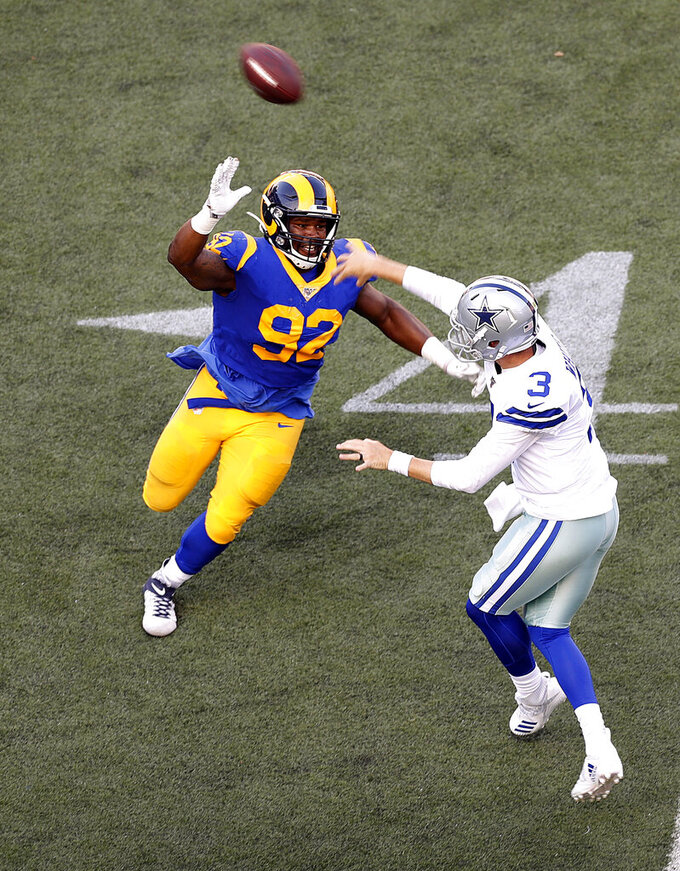 Los Angeles Rams defensive tackle Tanzel Smart (92) tries to stop Dallas Cowboys quarterback Mike White (3) from completing a pass during the second quarter of a preseason NFL football game, Saturday, Aug. 17, 2019, in Honolulu. (AP Photo/Marco Garcia)