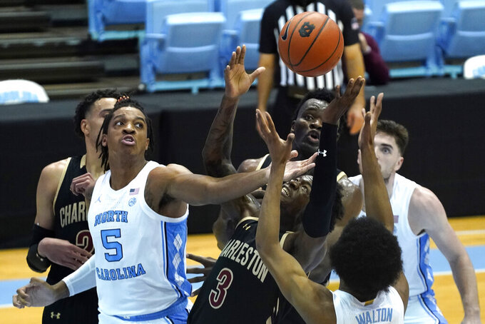 North Carolina forward Armando Bacot (5) reaches for a rebound with College of Charleston forward DeAngelo Epps (3) and center Osinachi Smart, rear, during the first half of an NCAA college basketball game in Chapel Hill, N.C., Wednesday, Nov. 25, 2020. (AP Photo/Gerry Broome)