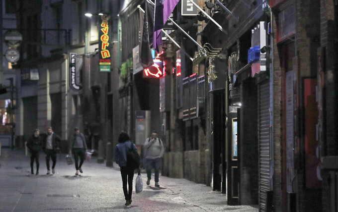 FILE - In this Oct. 14, 2020, file photo, people walk past closed bars as new measures across the region are set to come into force in Liverpool, England. After entire nations were shut down during the first surge of the coronavirus earlier this year, some countries and U.S. states are trying more targeted measures as cases rise again around the world, especially in Europe and the Americas. (AP Photo/Frank Augstein, File)