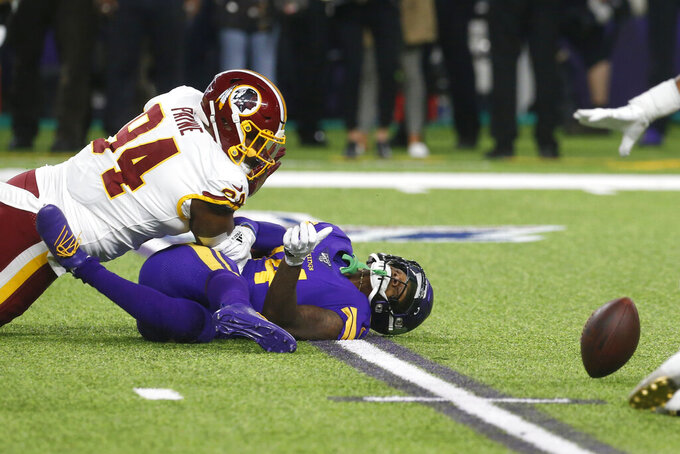 Minnesota Vikings wide receiver Stefon Diggs fumbles the ball after getting tackled by Washington Redskins nose tackle Daron Payne (94) during the first half of an NFL football game, Thursday, Oct. 24, 2019, in Minneapolis. (AP Photo/Jim Mone)
