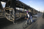 A cycler rides past a bus that was set on fire during overnight protests triggered by the death of a man who was detained by police for violating social distancing rules to curb the spread of the coronavirus in Bogota, Thursday, Sept. 10, 2020. Javier Ordonez died in a hospital after receiving repeated electric shocks with a stun gun from officers who detained him, seen on a video taken by Ordonez's friend, and published on social media. Authorities announced that the police involved were relieved of their duties as an investigation opens. (AP Photo/Fernando Vergara)