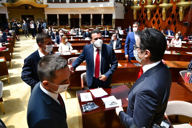 Zoran Zaev, the leader of the social democrats (SDSM), center, talks to the country's President Stevo Pendarovski, right, prior the constitutive session of the Parliament, in a dome hall at the parliament building in Skopje, North Macedonia, Tuesday, Aug. 4, 2020. North Macedonia has constituted its new parliament on Tuesday with strict protocols due to COVID-19 pandemic, with parties involved in July 15 snap elections now to start a complicated power-sharing negotiations after none of the main runners have won a needed majority in a 120-member parliament. (Press Service of the Parliament of North Macedonia via AP)