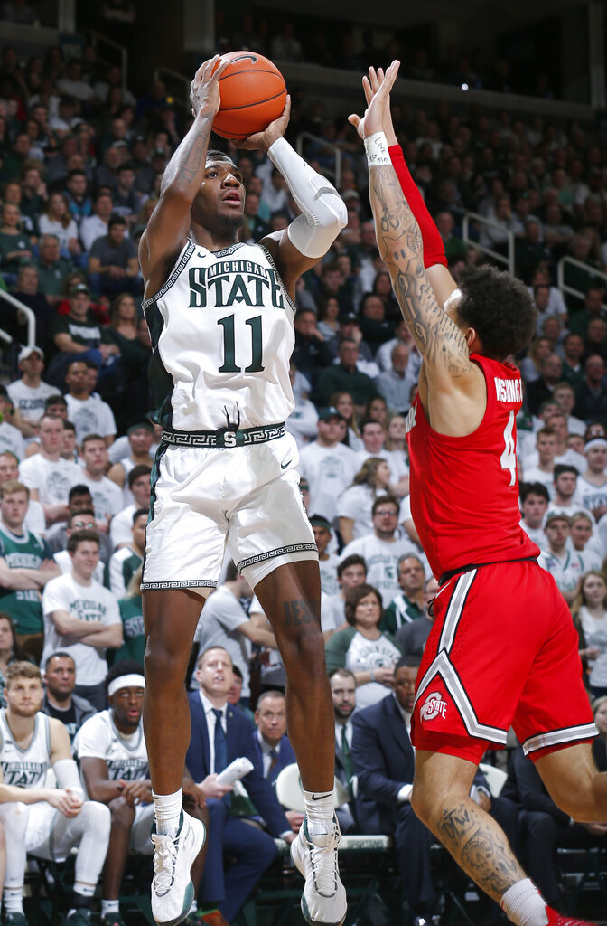 FILE - Michigan State's Aaron Henry, left, shoots against Ohio State's Duane Washington Jr. during the second half of an NCAA college basketball game in East Lansing, Mich., in this Sunday, March 8, 2020, file photo. Michigan State won 80-69. The team will need preseason All-Big Ten player Aaron Henry to produce much more than he has in the past as a role player.(AP Photo/Al Goldis, File)