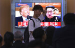 People watch a TV screen showing file footage of U.S. President Donald Trump, left, and North Korean leader Kim Jong Un during a news program at the Seoul Railway Station in Seoul, South Korea, Thursday, May 24, 2018. North Korea carried out what it said is the demolition of its nuclear test site Thursday, setting off a series of explosions over several hours in the presence of foreign journalists.The signs read: