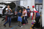 Migrants who were lodging at the AMAR migrant shelter get off the Pastor's vehicle to go to the Mexican immigration office on International Bridge 1, before being taken to apply for asylum on the United States side, in Nuevo Laredo, Mexico, Wednesday, July 17, 2019. Asylum-seekers grappled to understand what a new U.S. policy that all but eliminates refugee claims by Central Americans and many others meant for their bids to find a better life in America amid a chaos of rumors, confusion and fear. (AP Photo/Marco Ugarte)