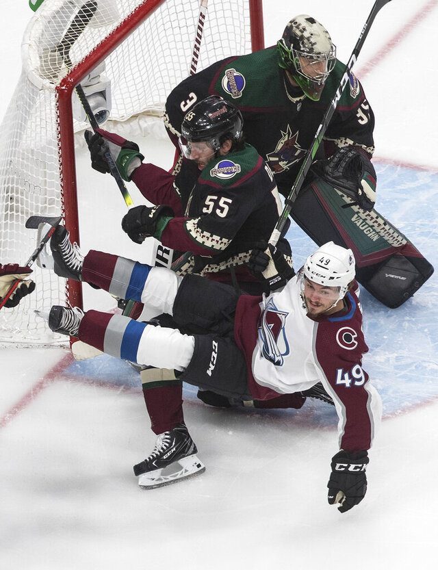 Colorado Avalanche's Samuel Girard (49) is checked by Arizona Coyotes' Jason Demers (55) as goalie Darcy Kuemper (35) looks for the shot during the first period in Game 4 of an NHL hockey first-round playoff series in Edmonton, Alberta, Monday, Aug. 17, 2020. (Jason Franson/The Canadian Press via AP)