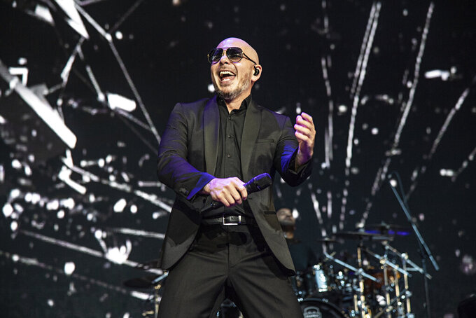 "FILE - This May 12, 2019 file photo shows Pitbull performing at KAABOO Texas in Arlington, Texas. Pitbull released a new song titled ""I Believe That We Will Win"" hoping to uplift his fans during the coronavirus pandemic. (Photo by Amy Harris/Invision/AP, File)"