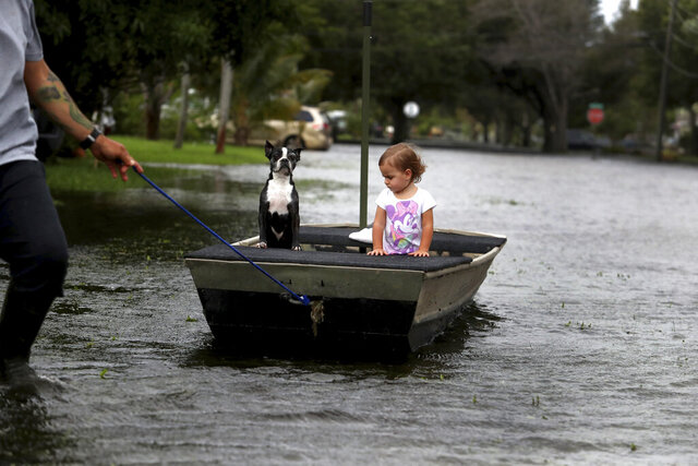 Lemay Acosta pulls his daughter Layla, 2, and dog Buster on a boat as they tour his flooded neighborhood in Plantation, Fla., on Monday, Nov. 9, 2020, a day after Tropical Storm Eta made landfall in the Florida Keys and flooded parts of South Florida. (Carline Jean/South Florida Sun-Sentinel via AP)