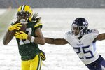 Green Bay Packers' Davante Adams catches a touchdown pass during the first half of an NFL football game against the Tennessee Titans Sunday, Dec. 27, 2020, in Green Bay, Wis. (AP Photo/Mike Roemer)
