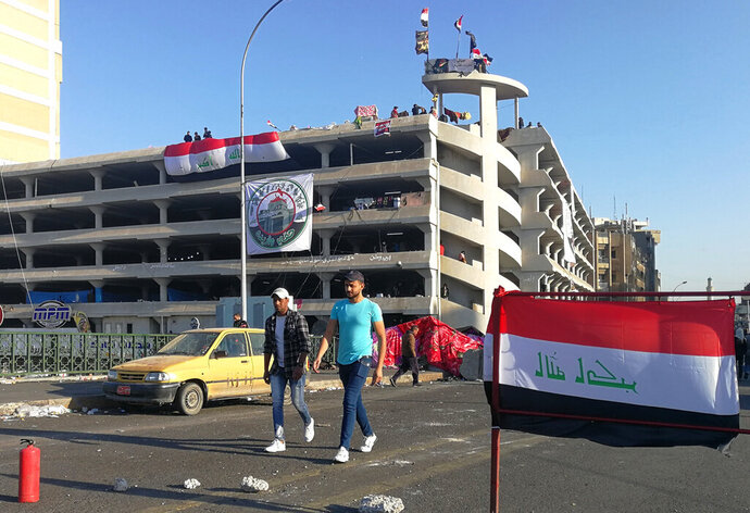 Anti-government protesters gather near the Sinak bridge leading to the Green Zone government areas during ongoing protests, in Baghdad, Iraq, Sunday, Nov. 17, 2019. (AP Photo/Khalid Mohammed)