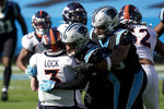 Denver Broncos quarterback Drew Lock is sacked by Carolina Panthers safety Jeremy Chinn and defensive end Austin Larkin during the first half of an NFL football game Sunday, Dec. 13, 2020, in Charlotte, N.C. (AP Photo/Gerry Broome)
