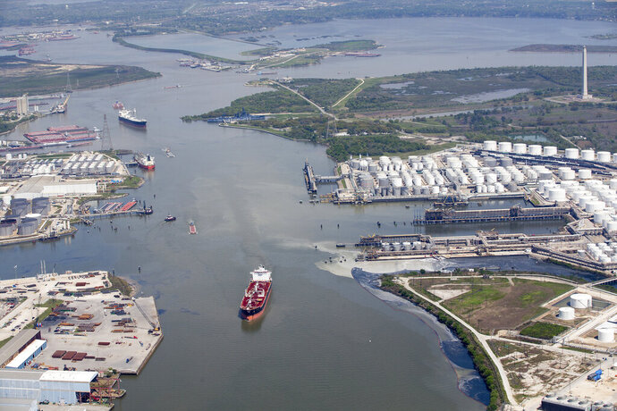 In a Wednesday, March 20, 2019 photo, maritime traffic moves through the Houston Ship Chanel past the site of now-extinguished petrochemical tank fire at Intercontinental Terminals Company in Deer Park, Texas. Air quality and water pollution from the fire's runoff, seen on the right, into the ship channel are some of the concerns in the aftermath of the blaze. (Brett Coomer/Houston Chronicle via AP)