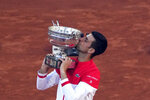 FILE- In this June 13, 2021, file photo, Serbia's Novak Djokovic kisses the trophy after defeating Stefanos Tsitsipas, of Greece, 6-7 (6), 2-6, 6-3, 6-2, 6-4 in the final of the French Open tennis tournament at the Roland Garros stadium in Paris. Djokovic is 26-0 in Grand Slam matches in 2021, moving him two victories away from being the first man to win all four major tennis championships in one season since Rod Laver in 1969. (AP Photo/Christophe Ena, File)
