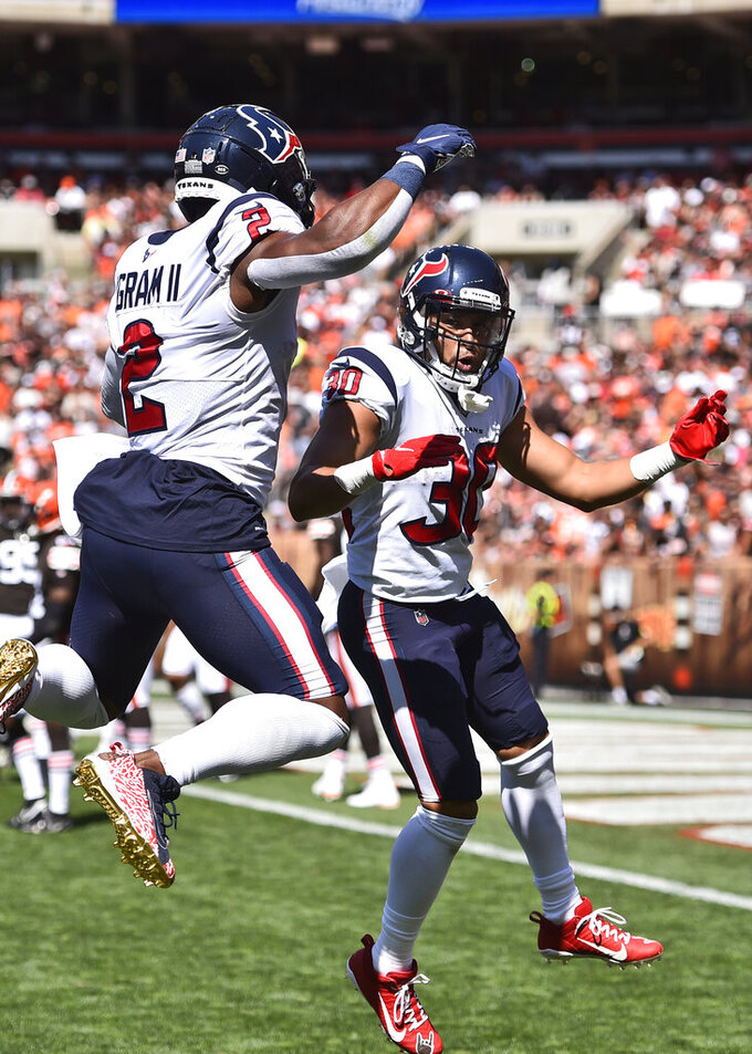 Houston Texans running back Phillip Lindsay (30) and Mark Ingram celebrate after Lindsay scored a 22-yard touchdown during the first half of an NFL football game against the Cleveland Browns, Sunday, Sept. 19, 2021, in Cleveland. (AP Photo/David Richard)