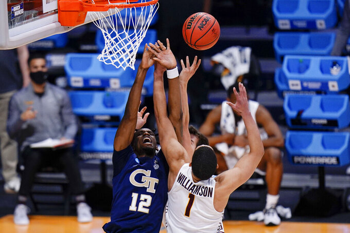 Georgia Tech forward Khalid Moore (12) goes up for a rebound in front of Loyola Chicago guard Lucas Williamson (1) in the first half of a college basketball game in the first round of the NCAA tournament at Hinkle Fieldhouse, Indianapolis, Friday, March 19, 2021. (AP Photo/AJ Mast)