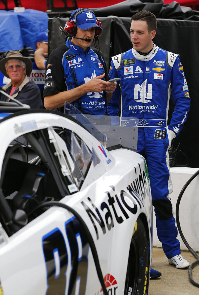 Alex Bowman, right, talks with a member of his crew prior to qualifying for Saturday's NASCAR Cup auto race at Richmond International Raceway in Richmond, Va., Friday, April 12, 2019. (AP Photo/Steve Helber)