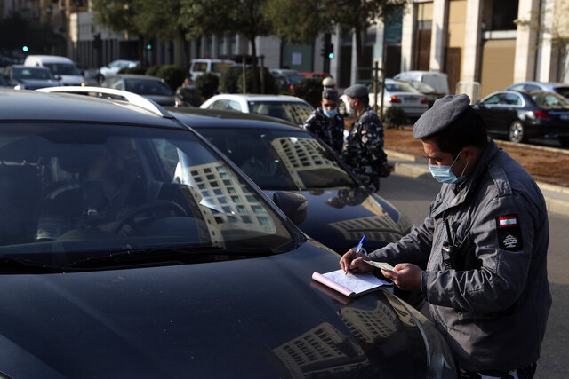 A police officer issues fines on vehicles that violate the odd and even license plate rule on alternating days as the country began a three-week lockdown to limit the spread of coronavirus amid a post-holiday surge in the past 10 days in Beirut, Lebanon, Thursday, Jan. 7, 2021. (AP Photo/Bilal Hussein)