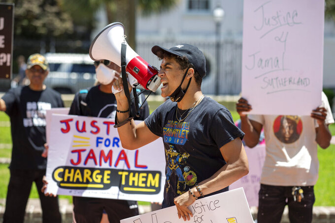 Elijah Whiteside leads protesters in a chant outside of Solicitor Scarlett Wilson's office in the Charleston County Judicial Center, Friday, May 21, 2021, in Charleston, S.C., to demand that the officers involved in the January death of Jamal Sutherland be charged. Video released by authorities earlier this year show deputies forcing Sutherland to the ground on his stomach and repeatedly shooting with him stun guns and pepper spray shortly before his death. The county coroner changed the death certificate earlier this month to indicate that Sutherland died by homicide, according to his family's attorneys. (Lauren Petracca/The Post And Courier via AP)