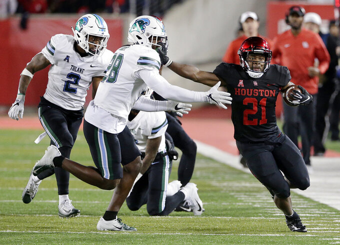 Houston running back Patrick Carr (21) pushes off Tulane linebacker Marvin Moody (28) during the first half of an NCAA college football game Thursday, Nov. 15, 2018, in Houston. (Michael Wyke/Houston Chronicle via AP)