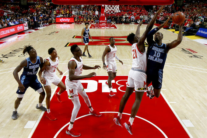 Rhode Island forward Cyril Langevine (10) goes up for a shot over Maryland forward Makhi Mitchell (21) during the first half of an NCAA college basketball game Saturday, Nov. 9, 2019, in College Park, Md. Maryland won 73-55. (AP Photo/Julio Cortez)