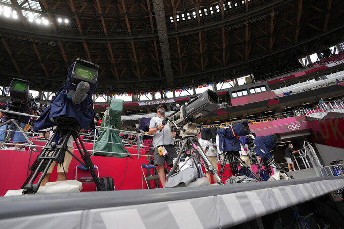 Cameramen work at the 2020 Summer Olympics, Saturday, July 31, 2021, in Tokyo. The willingness of athletes, led by Simone Biles, to talk about the pressures they face as elite athletes on the Olympics stage, has forced a look at how NBC presents the Games to the public. (AP Photo/Petr David Josek)