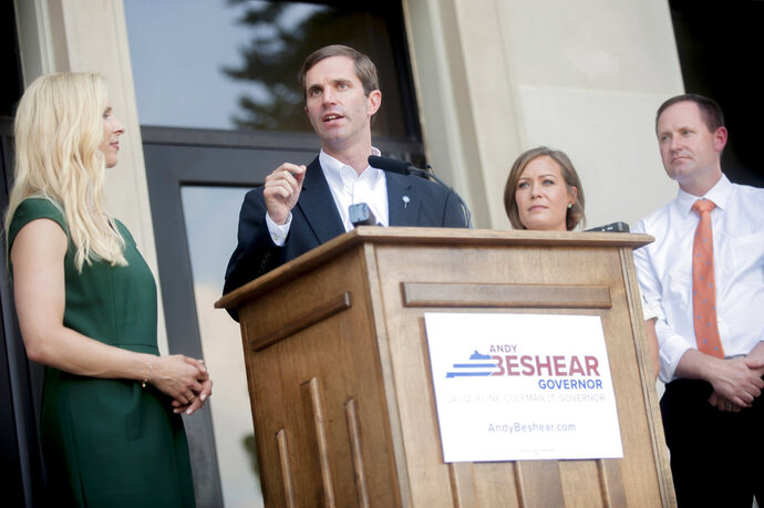 Attorney General Andy Beshear, center, speaks next to his wife Britainy Beshear, left, running mate Jacqueline Coleman, and her husband Chris O'Bryan, while Beshear discusses his announcement to run for governor at Western Kentucky University's Cherry Hall Tuesday, July 10, 2018, in Bowling Green, Ky. Beshear announced Monday he will seek the Democratic nomination for governor in 2019. (Bac Totrong/Daily News via AP)