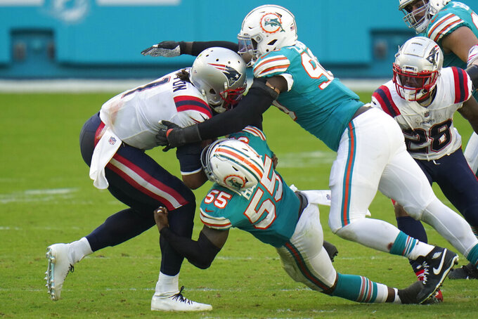 Miami Dolphins outside linebackers Shaq Lawson (90) and Jerome Baker (55) sack New England Patriots quarterback Cam Newton (1) during the second half of an NFL football game, Sunday, Dec. 20, 2020, in Miami Gardens, Fla. The Dolphins defeated the Patriots 22-12. (AP Photo/Chris O'Meara)