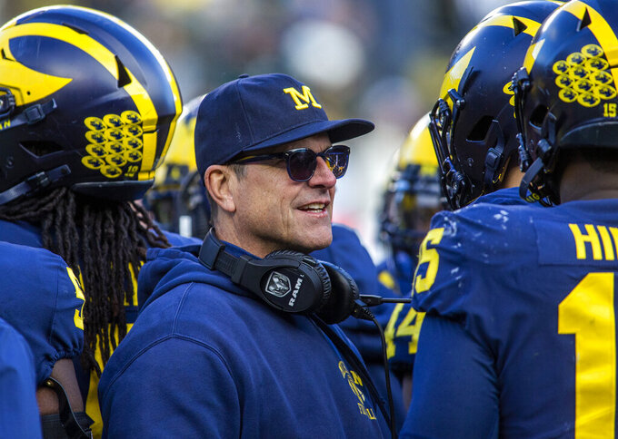 FILE  - In this Nov. 16, 2019, file photo, Michigan head coach Jim Harbaugh huddles with his players on the field during a time out in the fourth quarter of an NCAA college football game against Michigan State in Ann Arbor, Mich. Jim Harbaugh enters his sixth season as Michigan's coach with just two years left on his contract, adding another layer of interest in the 18th-ranked Wolverines as they kick off the season this week at No. 21 Minnesota.  (AP Photo/Tony Ding, File)