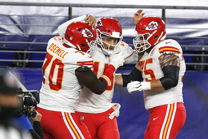 Kansas City Chiefs offensive guard Kelechi Osemele, left, quarterback Patrick Mahomes and offensive tackle Mike Remmers celebrate Mahomes touchdown during the first half of an NFL football game against the Baltimore Ravens, Monday, Sept. 28, 2020, in Baltimore. (AP Photo/Nick Wass)