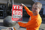 Anti-tax activist Tim Eyman poses for a photo with a sign from his original 1999 campaign for $30 car registration tabs, Tuesday, Nov. 5, 2019, as he waved a sign for his current Initiative 976 on election day in Bellevue, Wash. The measure would again cut most car tabs to $30 in Washington state, if passed by voters, and would leave state and local governments scrambling to pay for road paving and other transportation projects. (AP Photo/Ted S. Warren)